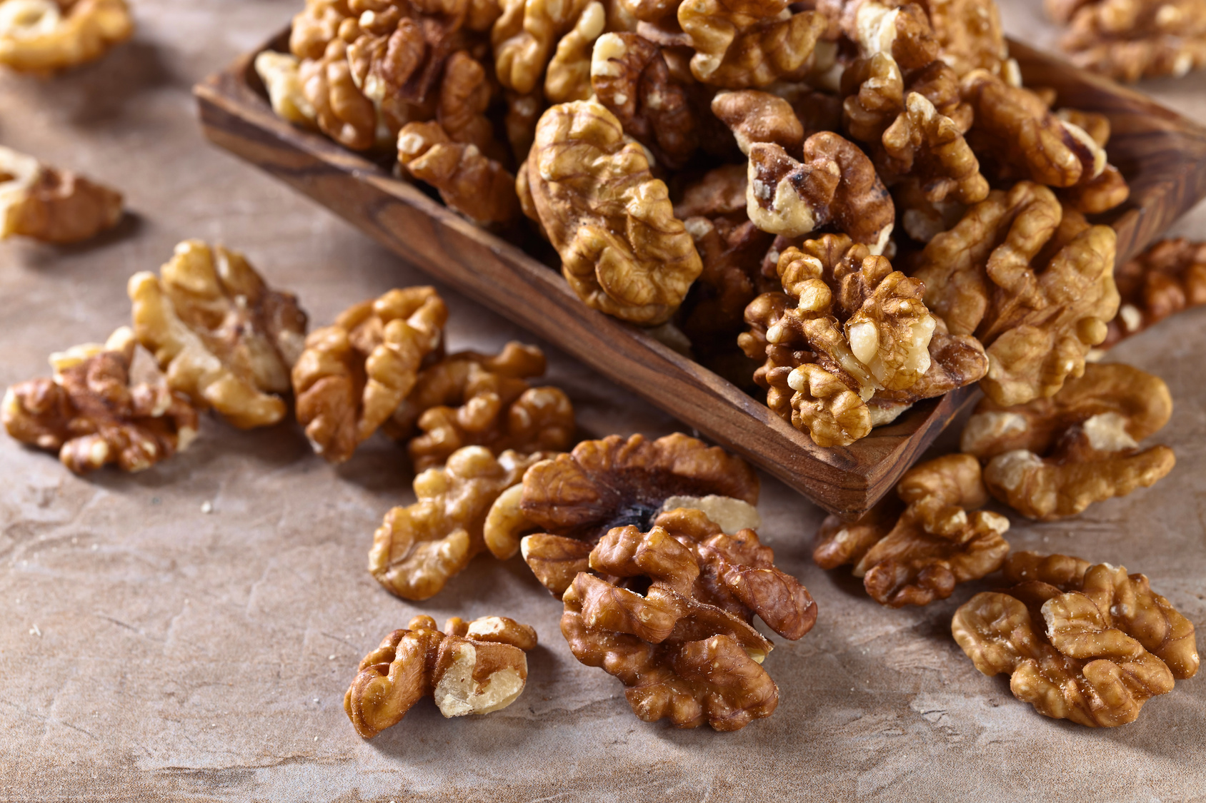 Walnuts in old wooden dish on a kitchen table