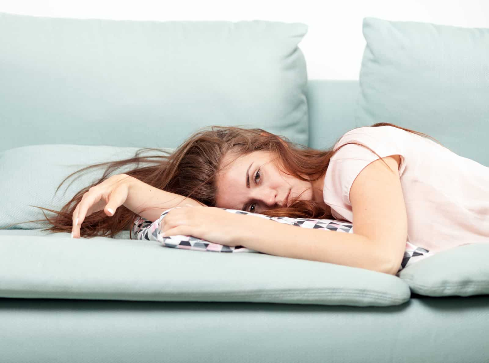 Exhausted young woman lying on couch at home, casual style indoor shoot