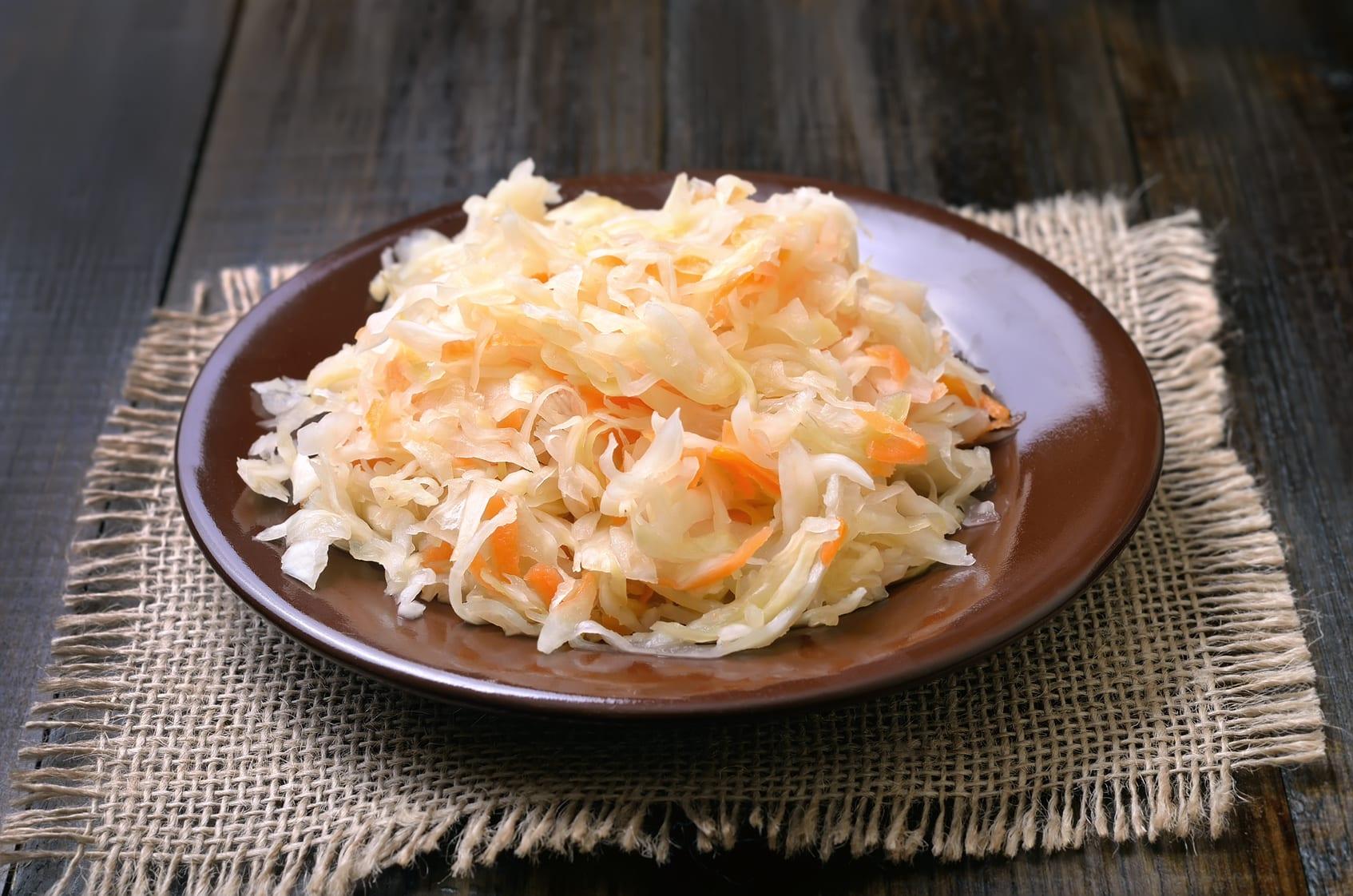 Sauerkraut on ceramic plate on wooden table